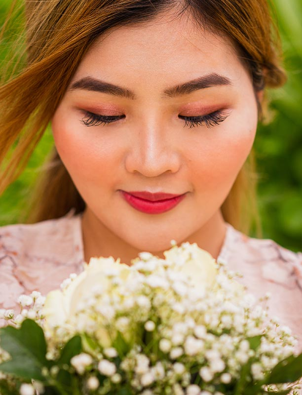 This photo shows Asian bride closeup with bridal bouquet