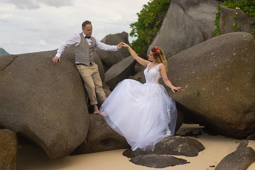 This photo shows bride and groom between large rocks