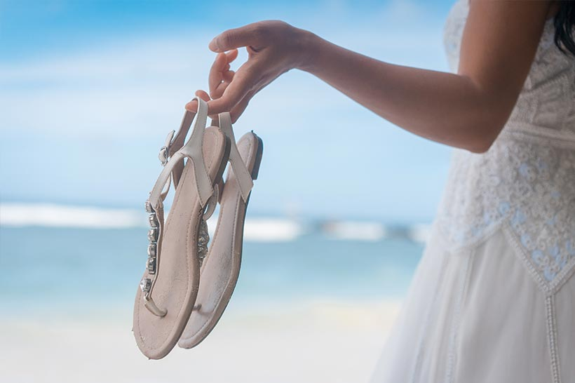 This photo shows a bride holding her flip flops