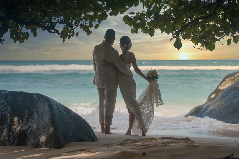 This photo shows bride and groom at the shoreline at sunset looking to the ocean