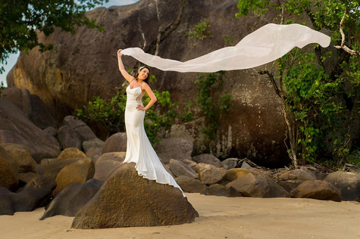 This photo shows a bride waiving a very long veil in the wind