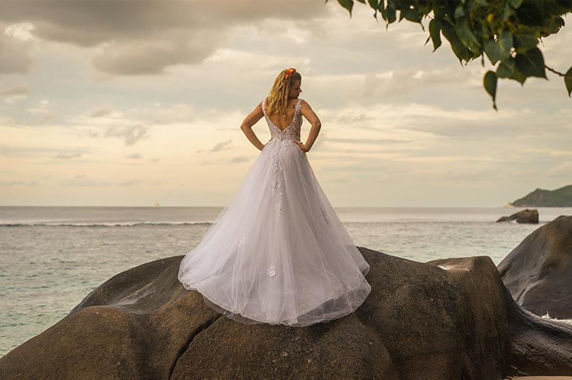 This photo shows a stunning bride at sunset at the beach standing on a rock