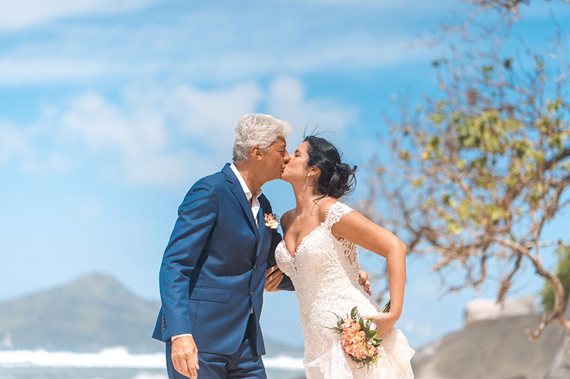 This photo shows a cheerful wedding couple at the beach, Mahe