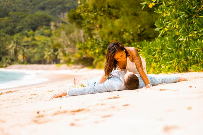 This photo shows a cheerful couple laying on the sand