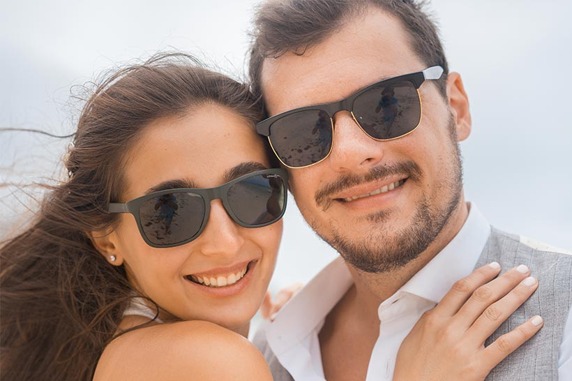 This photo shows happy bride & groom closeup with sunglasses