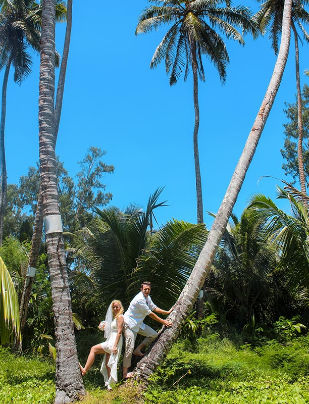 This photo shows bride & groom between 2 large palm trees
