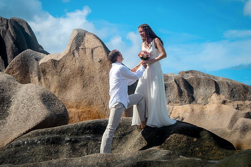 This Photo shows couple climbing a rock