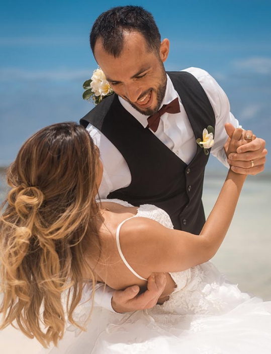 This photo shows a couple in happy mood dancing at the beach