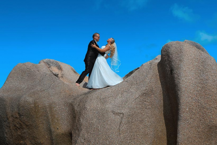 This Photo shows a couple posing on large granite rocks