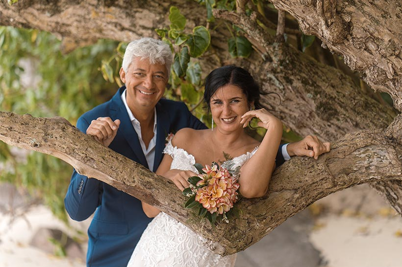 This photo shows a couple posing under a tree at Glacis, Mahe