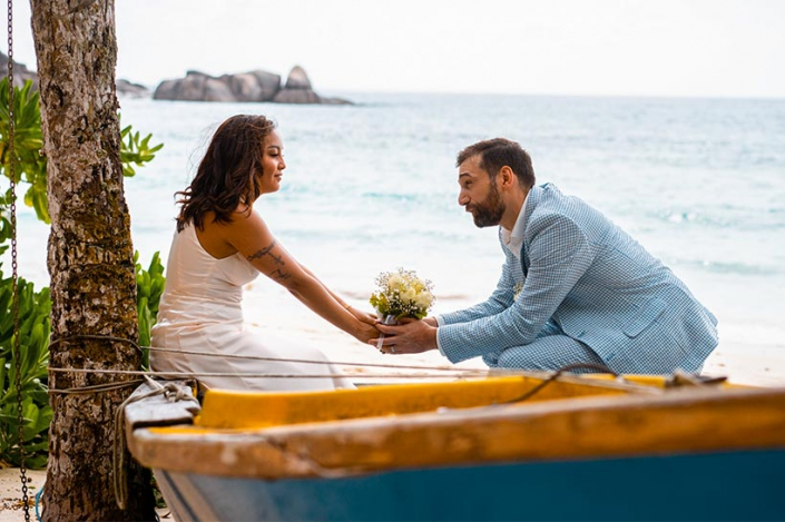 This photo shows a cheerful couple sitting in a fishing boat, Anse Takama Mahe