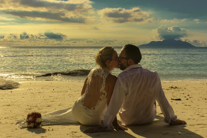 This Photo shows a couple sitting in the sand, kissing