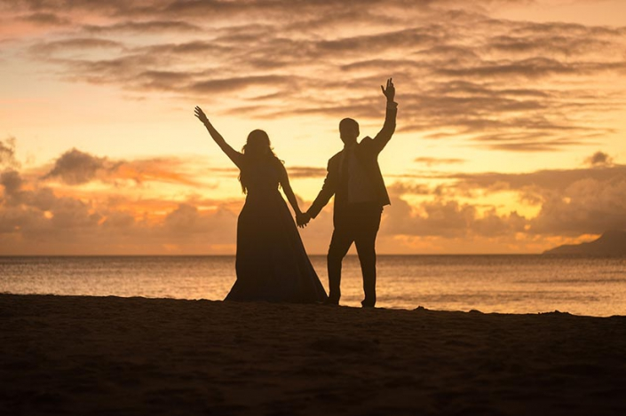 This photo shows anazing sunset in Seychelles with cheerful wedding couple