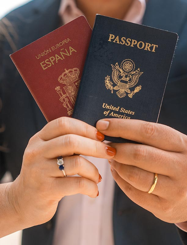 This photo shows a closeup couple holding up their passports
