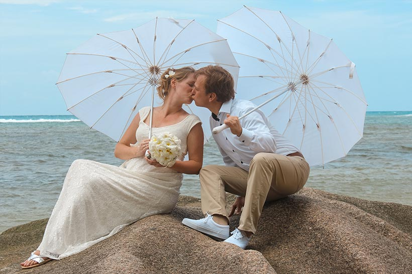 This photo shows a couple with umbrellas to protect from sun
