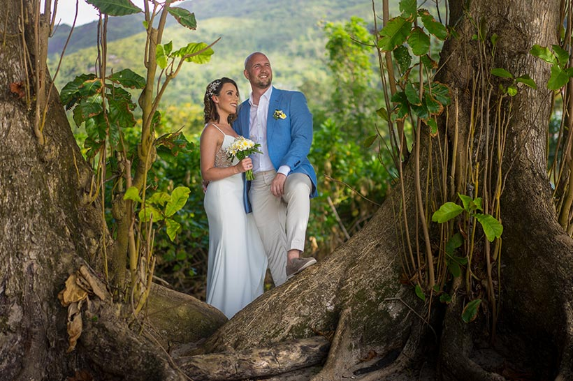 This photo shows bride & groom posing between 2 trees at Bel Ombre beach