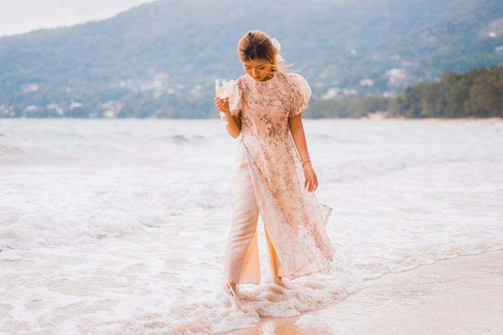 This photo shows a happy bride walking at the beach