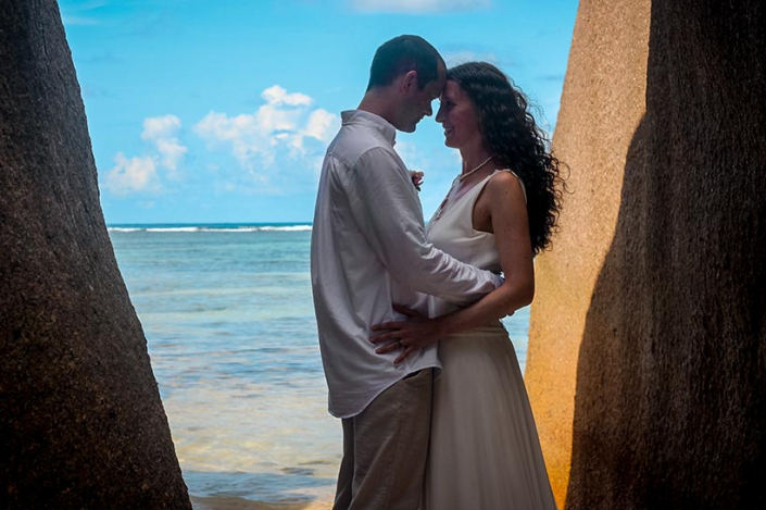 This Photo shows a gleeful bride & groom looking to the ocean