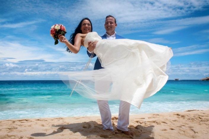 This Photo shows a groom carrying the bride