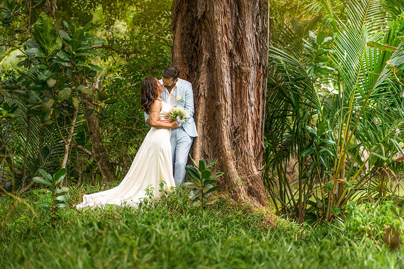 This photo shows the wedding couple leaning on a large tree