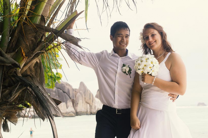 This Photo shows a young lovely couple posing at a palmtree