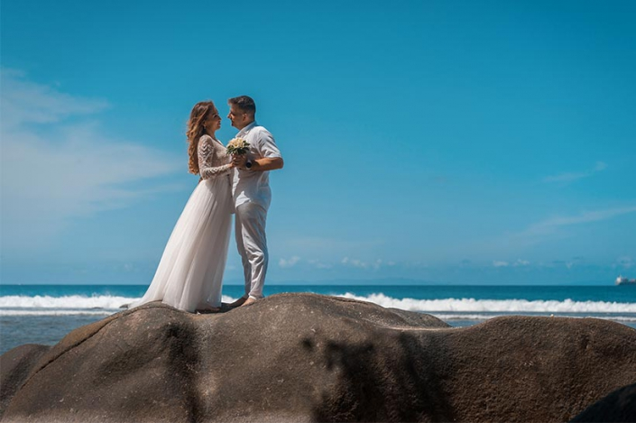 This photo shows a lucky wedding couple standing on a large rock