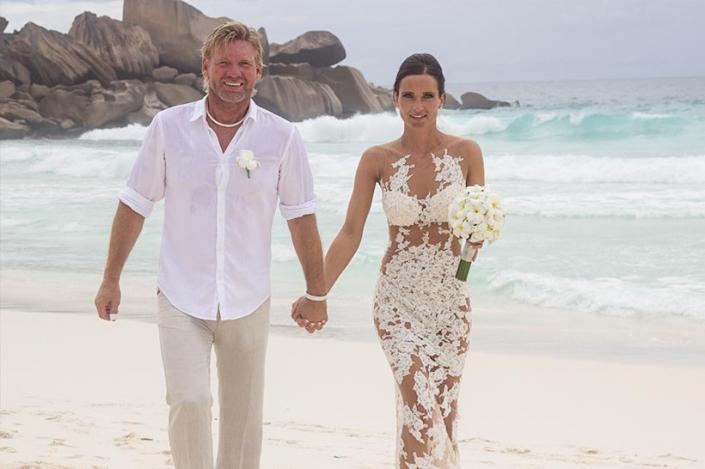 This Photo shows a happy couple couple walking alongside the beach, La Digue