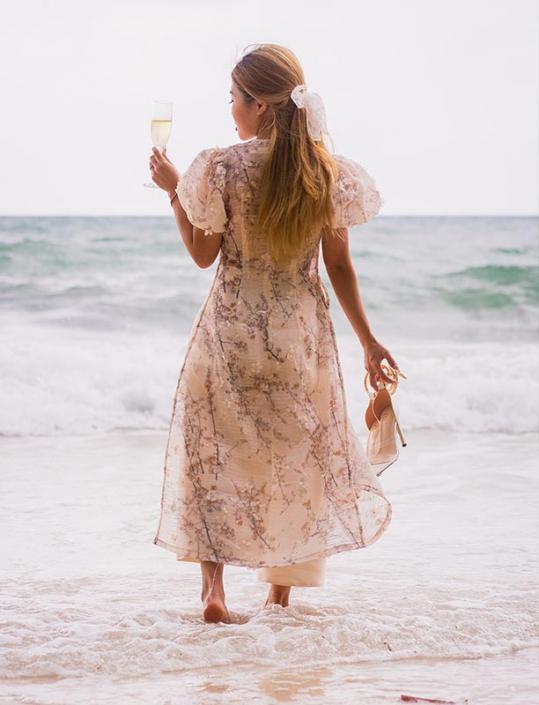 This photo shows a vietnamese bride walking the shoreline