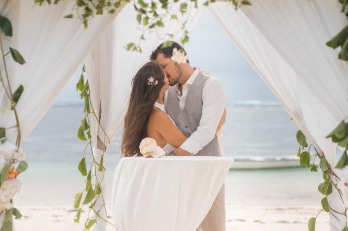 This photo shows a beach wedding pavilion with couple
