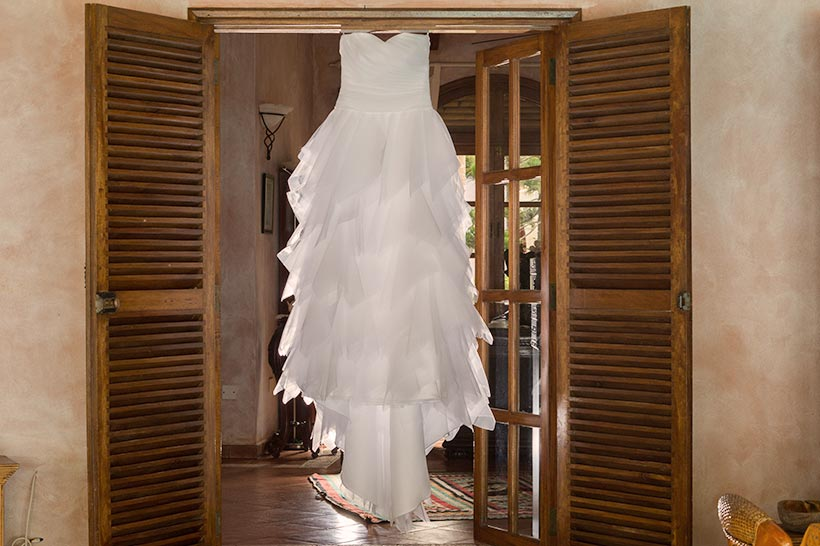 This Photo shows the brides wedding dress hanging from the door frame