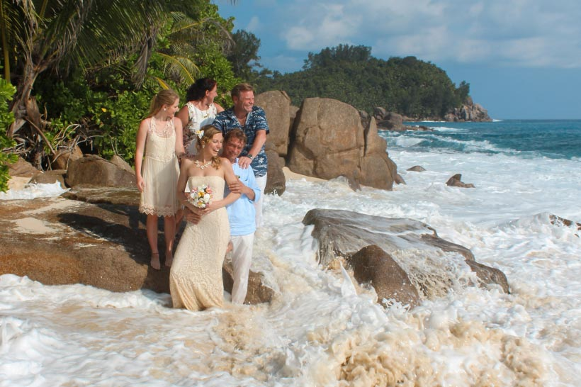 This photo shows exited wedding group at the beach with wave coming in